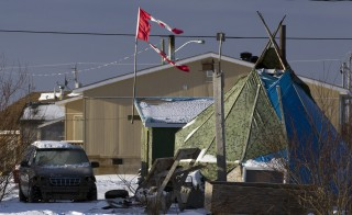 A tattered Canadian flag flies over a teepee in Attawapiskat, Ontario, December 17, 2011. About 20 families will move into a temporary shelter on December 23 to escape the housing crisis at the aboriginal reserve of Attawapiskat where many households live without running water or sanitary facilities, according to local media. Photo by Frank Gunn/Pool/via Reuters