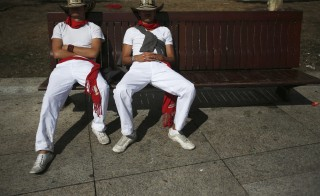 Two men sleep on a bench following the running of the bulls in Pamplona, Spain in 2012. Photo by Susana Vera/Reuters