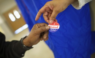 Voting machine operator Robin Coffee-Ruff hands a sticker to a voter who cast his ballot at West Philadelphia High School on U.S. midterm election day morning in Philadelphia, Pennsylvania, November 4, 2014.  REUTERS/Mark Makela (UNITED STATES - Tags: POLITICS ELECTIONS) - RTR4CT7R