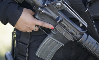 A female member of the Fuerza Civil (Civil Force) police unit holds her weapon during a patrol at an impoverished neighbourhood in Monterrey February 26, 2015. Fuerza Civil, a tactical team of the police unit trained by the army, was created by the Nuevo Leon government in 2011 to curb down corruption and infiltration by drug gangs in the police corps, local media reported. Promising a new law to stop the infiltration of local governments by organized crime, President Enrique Pena Nieto pledged to reform the penal system and send a proposal to Congress to unify multi-layered police forces in Mexico's 31 states, taking Fuerza Civil as the police model that the federal government wants for the rest of the country. REUTERS/Daniel Becerril (MEXICO - Tags: CIVIL UNREST POLITICS CRIME LAW) - RTR4RCUU