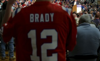 A man wearing a jersey of New England Patriots quarterback Tom Brady listens as Republican presidential candidate Donald Trump speaks at a campaign town hall meeting in Rochester, New Hampshire. Photo by Brian Snyder/Reuters