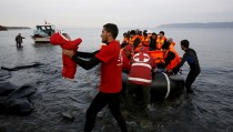 A Red Cross volunteer carries a Syrian refugee baby off an overcrowded raft at a beach on the Greek island of Lesbos November 16, 2015. Of the 660,000 refugees and migrants who have reached Greece this year, more than half have landed at Lesbos. So far this year, some 3,460 lives have been lost crossing the Mediterranean, 360 in the last four weeks alone with 250 of these in Greek territorial waters, UNHCR spokesperson Adrian Edwards told a news briefing in Geneva on November 13.  REUTERS/Yannis Behrakis      TPX IMAGES OF THE DAY      - RTS7BGP