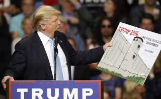Republican presidential candidate Donald Trump holds a sign supporting his plan to build a wall between the United States and Mexico that he borrowed from a member of the audience at his campaign rally in Fayetteville, North Carolina. Photo by Jonathan Drake/Reuters