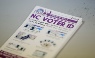 """A pile of government pamphlets explaining North Carolina's controversial """"Voter ID"""" law sits on table at a polling station as the law goes into effect for the state's presidential primary in Charlotte, North Carolina March 15, 2016. REUTERS/Chris Keane - RTSAI74"""