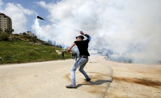 A Palestinian protester uses a sling to launch a tear gas canister, initially fired by Israeli troops, during clashes at a protest marking Land Day, near Israel's Ofer Prison near the West Bank city of Ramallah March 30, 2016. March 30 marks Land Day, the annual commemoration of protests in 1976 against Israel's appropriation of Arab-owned land in the Galilee. REUTERS/Mohamad Torokman         TPX IMAGES OF THE DAY      - RTSCUJY