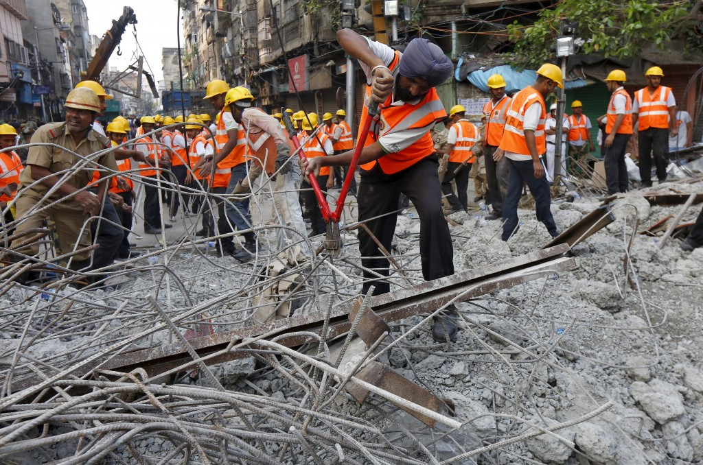 A rescue worker cuts iron rods amidst the debris at the site of an under-construction flyover that collapsed on Thursday in Kolkata, April 1, 2016. REUTERS/Rupak De Chowdhuri - RTSD515