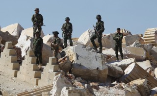 "Syrian army soldiers stands on the ruins of the Temple of Bel in the historic city of Palmyra, in Homs Governorate, Syria April 1, 2016. More than 40 bodies were discovered this week in a mass grave that included some women and children, the Syrian government said.  Omar Sanadiki/Reuters SEARCH ""PALMYRA SANADIKI"" FOR THIS STORY. SEARCH ""THE WIDER IMAGE"" FOR ALL STORIES - RTSD6ME"