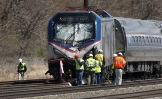 Emergency personnel examine the scene after an Amtrak passenger train struck a backhoe, killing two people, in Chester, Pennsylvania, April 3, 2016. The southbound Palmetto train running from New York to Savannah, Georgia, had about 341 passengers and seven crew members aboard when it struck the backhoe. REUTERS/Dominick Reuter       TPX IMAGES OF THE DAY      - RTSDDQD