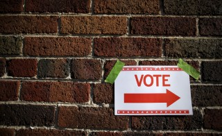 A sign is taped to a brick wall outside a polling station for the Wisconsin presidential primary election in Milwaukee, Wisconsin, United States, April 5, 2016.     REUTERS/Jim Young  - RTSDPLZ