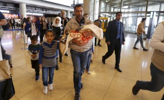 Syrian refugee Ahmad al Aboud, and his family members, who will be resettled in the United States as part of a refugee admissions programme, walk to board their plane at the Queen Alia International Airport in Amman, Jordan, April 6,2016. REUTERS/Muhammad Hamed. - RTSDU4K