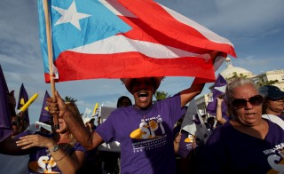A member of a labor union shouts slogans while holding a Puerto Rico flag during a protest in San Juan, Puerto in September 2015. Photo by Alvin Baez/Reuters