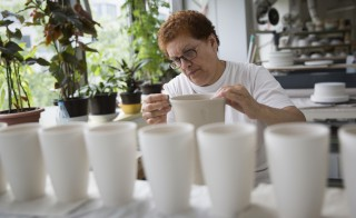 A woman polishes a vase at the KPM porcelain manufacturer in Berlin June 28, 2013. A recent study by consulting firm Ernst & Young showed three of every four German Mittelstand firms are struggling to find suitable employees due to an acute shortage of skilled labour. And that's not the only problem worrying the sector ahead of a federal election in September in which Chancellor Angela Merkel is seen likely to win a third term, in part due to the relative strength of the German economy. Joerg Woltmann, owner of KPM, a 250-year-old porcelain manufacturer in Berlin once owned by the German monarchy, said a rise in taxes would make firms like his, a 180-employee business with sales of 10 million euros last year, more vulnerable to crises by plundering company reserves. Picture taken June 28, 2013. REUTERS/Thomas Peter (GERMANY - Tags: BUSINESS POLITICS) - RTX11BY6