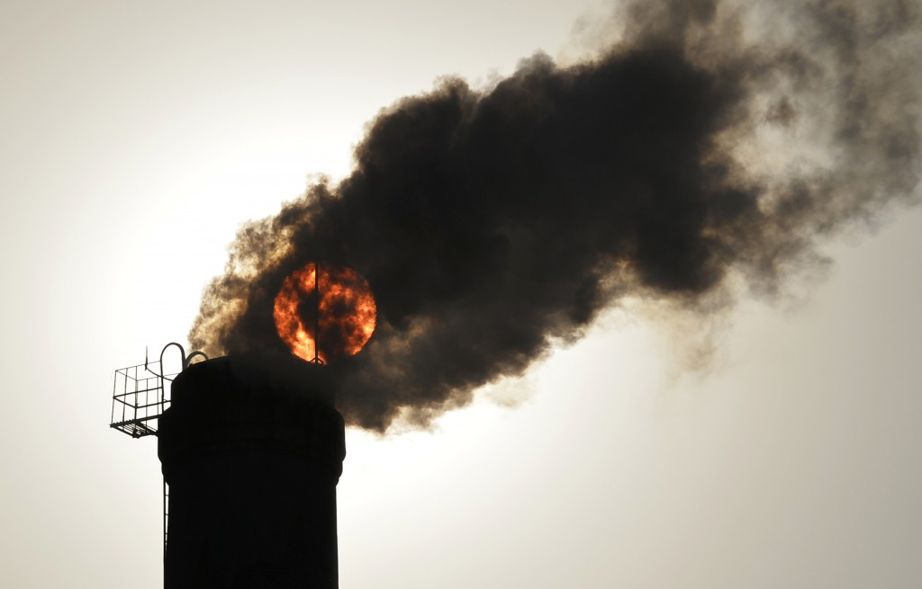 The sun is seen behind smoke billowing from a chimney of a heating plant in Taiyuan, Shanxi province in China on December 9, 2013. Photo by Stringer /REUTERS