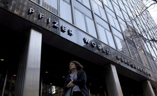 A woman passes by the Pfizer World Headquarters building in the Manhattan borough of New York, November 23, 2015.  Pfizer Inc  on Monday said it would buy Botox maker Allergan Plc  in a record-breaking deal worth $160 billion to cut its U.S. tax bill by moving its headquarters to Ireland.   REUTERS/Brendan McDermid - RTX1VI00