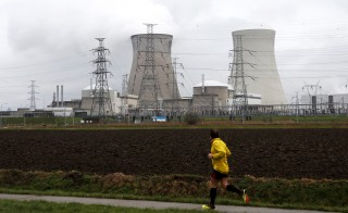 A man jogs past the cooling towers of the Doel nuclear plant of Electrabel, the Belgian unit of French company Engie, former GDF Suez, in Doel near Antwerp, Belgium, January 4, 2016.  REUTERS/Francois Lenoir  - RTX20Z09