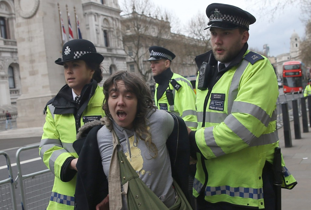 A demonstrator is detained by polilce officers during a protest outside Downing Street in Whitehall, central London, Britain April 9, 2016. British Prime Minister David Cameron said on Saturday he should have handled scrutiny of his family's tax arrangements better and promised to learn the lessons after days of negative media coverage and calls for his resignation  REUTERS/Neil Hall - RTX297LL
