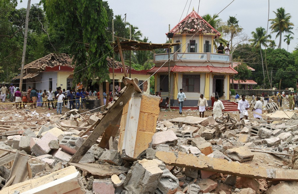 People stand next to debris after a broke out at a temple in Kollam in the southern state of Kerala, India, April 10, 2016. A huge fire swept through a temple in India's southern Kerala state early on Sunday (April 10), killing nearly 80 people and injuring over 200 gathered for a fireworks display to mark the start of the local Hindu new year. REUTERS/Sivaram V - RTX299XX