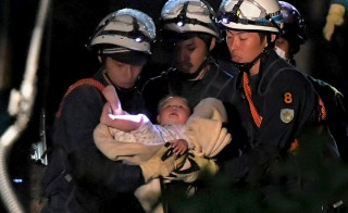 An eight-month-old baby is carried away by rescue workers after being rescued from her collapsed home caused by an earthquake in Mashiki town, Kumamoto prefecture, southern Japan, in this photo taken by Mainichi Shimbun April 15, 2016 early morning. Daisuke Wada/Mainichi Shimbun via Reuters