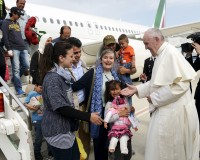 Pope Francis welcomes a group of Syrian refugees after landing at Ciampino airport in Rome following a visit at the Moria refugee camp in the Greek island of Lesbos, April 16, 2016. REUTERS/ Filippo Monteforte/Pool      TPX IMAGES OF THE DAY - RTX2A8LK