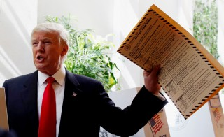 Republican presidential candidate Donald Trump lifts his ballot while voting for the New York primary election in the Manhattan borough of New York City, U.S., April 19, 2016.  REUTERS/Andrew Kelly  - RTX2AO0M