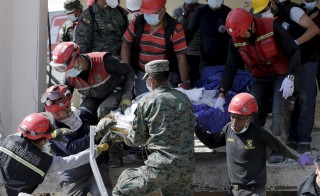 Soldiers and rescue team members carry the body of a victim at a collapsed building after an earthquake struck off the Pacific coast, in Pedernales, Ecuador, April 19, 2016. REUTERS/Henry Romero - RTX2AOYF