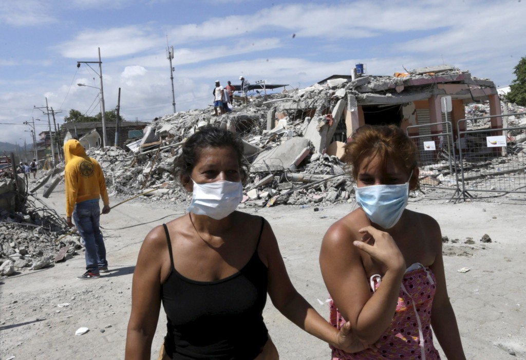 Residents walk past a collapsed home on April 19, 2016 after an earthquake struck off the Pacific coast, in Pedernales, Ecuador. Photo by Henry Romero/Reuters