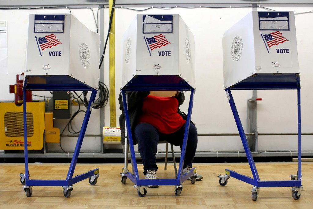 A person sits while completing a ballot at the polling center at the James Weldon Johnson Community Center during the New York primary elections in the East Harlem neighborhood of New York City, U.S., April 19, 2016. REUTERS/Andrew Kelly - RTX2AP2S