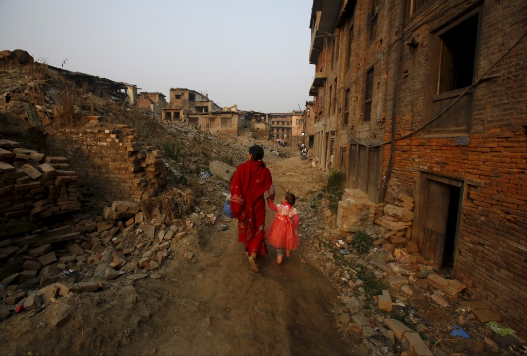 """A woman and a child walk past the remains of collapsed houses damaged during the April 2015 earthquake, in Bhaktapur, Nepal March 18, 2016. The two devastating earthquakes that struck Nepal last year killed almost 9,000 people across the country. Inside the Kathmandu Valley almost 2,000 died, and some of the area's most important cultural and heritage sites were completely destroyed.As Kathmandu inhabitants prepare to mark the one-year anniversary of the event, thousands are still displaced and millions are living in temporary shelters. REUTERS/Navesh Chitrakar SEARCH """"ANNIVERSARY QUAKE"""" FOR THIS STORY. SEARCH """"THE WIDER IMAGE"""" FOR ALL STORIES TPX IMAGES OF THE DAY TPX IMAGES OF THE DAY - RTX2B8EU"""