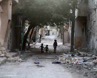 Children walk near garbage in al-Jazmati neighbourhood of Aleppo, Syria April 22, 2016. REUTERS/Abdalrhman          Ismail - RTX2B9AM