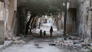 Children walk near garbage in al-Jazmati neighbourhood of Aleppo, Syria April 22, 2016. REUTERS/Abdalrhman Ismail - RTX2B9AM
