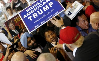 U.S. Republican presidential candidate Donald Trump signs autographs for supporters holding a Muslim Americans for Trump sign after a rally in Harrington, Delaware April 22, 2016. REUTERS/Jonathan Ernst - RTX2B9ZE
