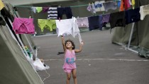 A girl is pictured next to a line of clothes hung out to dry outside a tent at the Reales Tamarindos airport which is used as a shelter, after being evacuated from her home in Portoviejo, after an earthquake struck off Ecuador's Pacific coast, April 22, 2016. REUTERS/Henry Romero - RTX2BA3T