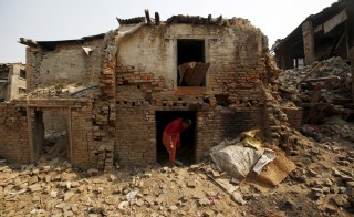A woman walks out from her house damaged during the 2015 earthquakes in Bhaktapur, Nepal, April 25, 2016. REUTERS/Navesh Chitrakar      TPX IMAGES OF THE DAY      - RTX2BJHQ