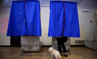 A voter with her dog casts her ballot in the Pennsylvania primary at a polling place in Philadelphia on April 26. Photo by Charles Mostoller/Reuters