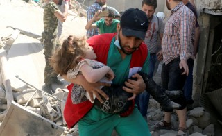 A man carries a child from the rubble caused by an airstrike in the rebel-held area of Old Aleppo, Syria on April 28. Photo by Abdalrhman Ismail/Reuters