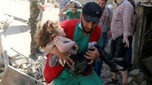 A civil defence member carries a child that survived from under the rubble at a site hit by airstrikes in the rebel held area of Old Aleppo, Syria, April 28, 2016. REUTERS/Abdalrhman Ismail     TPX IMAGES OF THE DAY      - RTX2C2IT