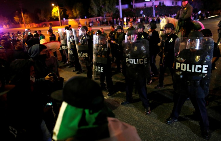 Police in riot gear arrive to break up a demonstration outside Republican presidential candidate Donald Trump's campaign rally in Costa Mesa, California on April 28. Photo by Mike Blake/Reuters
