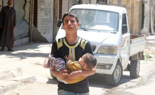A civilian evacuates a baby from a site hit by airstrikes in the rebel held area of Aleppo's al-Fardous district, Syria, April 29, 2016. Photo by Abdalrhman Ismail/Reuters