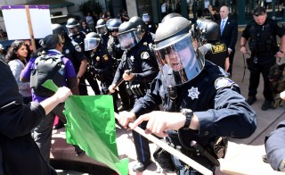 Police in riot gear hold back demonstrators against U.S. Republican presidential candidate Donald Trump outside the Hyatt hotel where Trump is set to speak at the California GOP convention in Burlingame, California, U.S., April 29, 2016. REUTERS/Noah Berger - RTX2C7BU