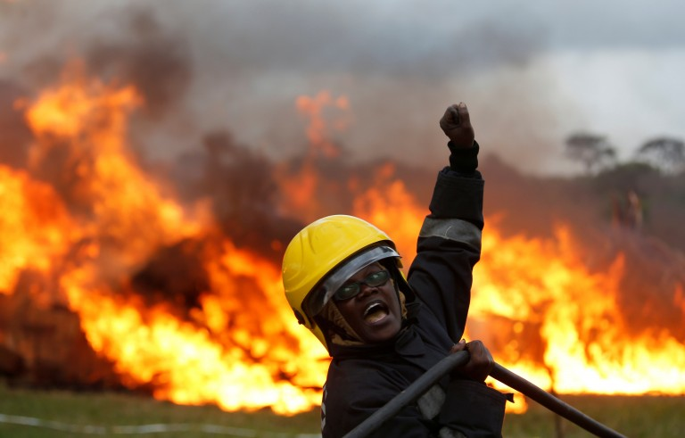 A member of the fire brigade shouts as she and other members control the burning of an estimated 105 tonnes of Elephant tusks confiscated ivory from smugglers and poachers at the Nairobi National Park near Nairobi, Kenya, April 30, 2016. REUTERS/Thomas Mukoya - RTX2C948