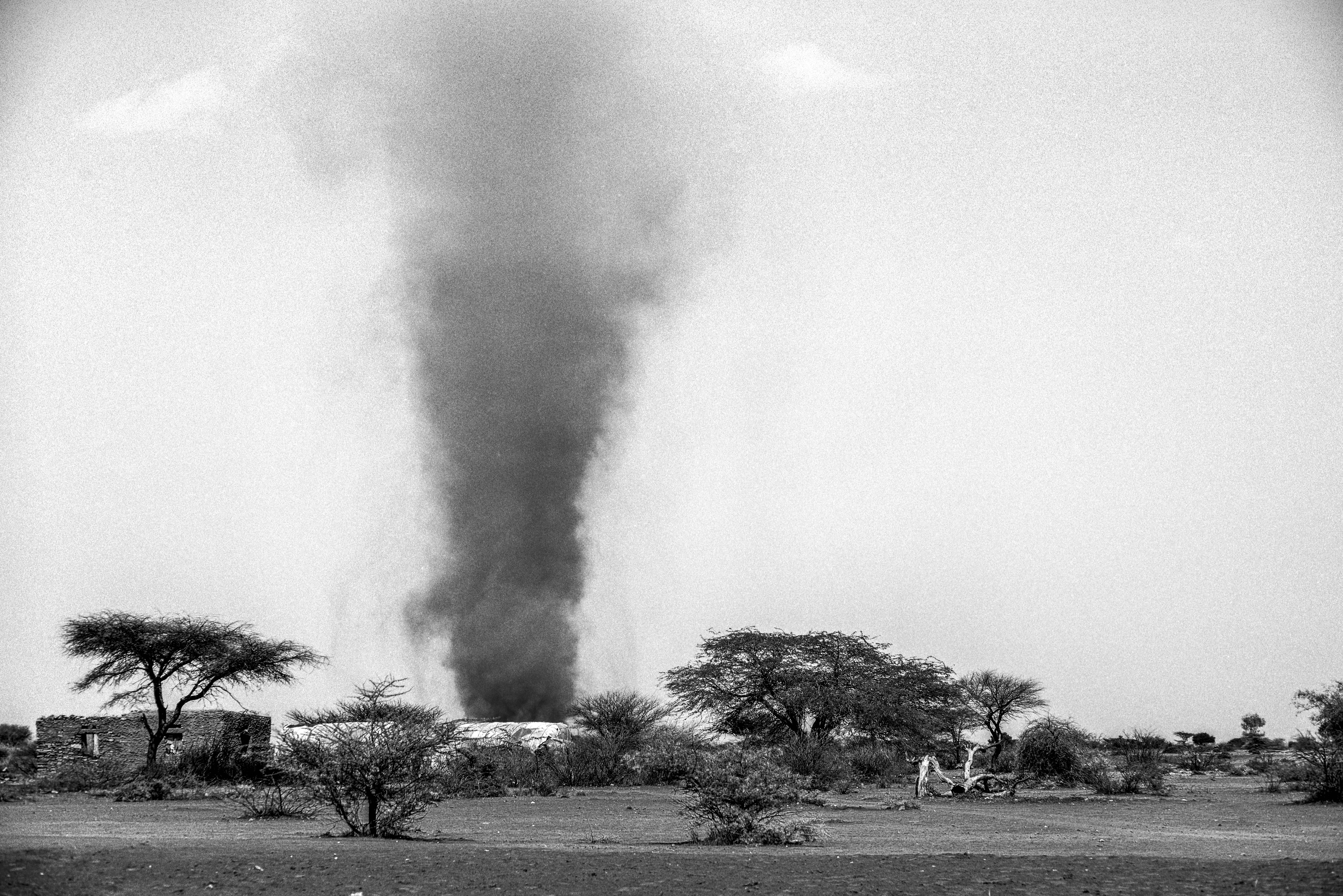 The searing heat creates a huge dust devil that cuts through a small village in the region of Somaliland in northern Somalia. Photo by Sebastian Rich for UNICEF