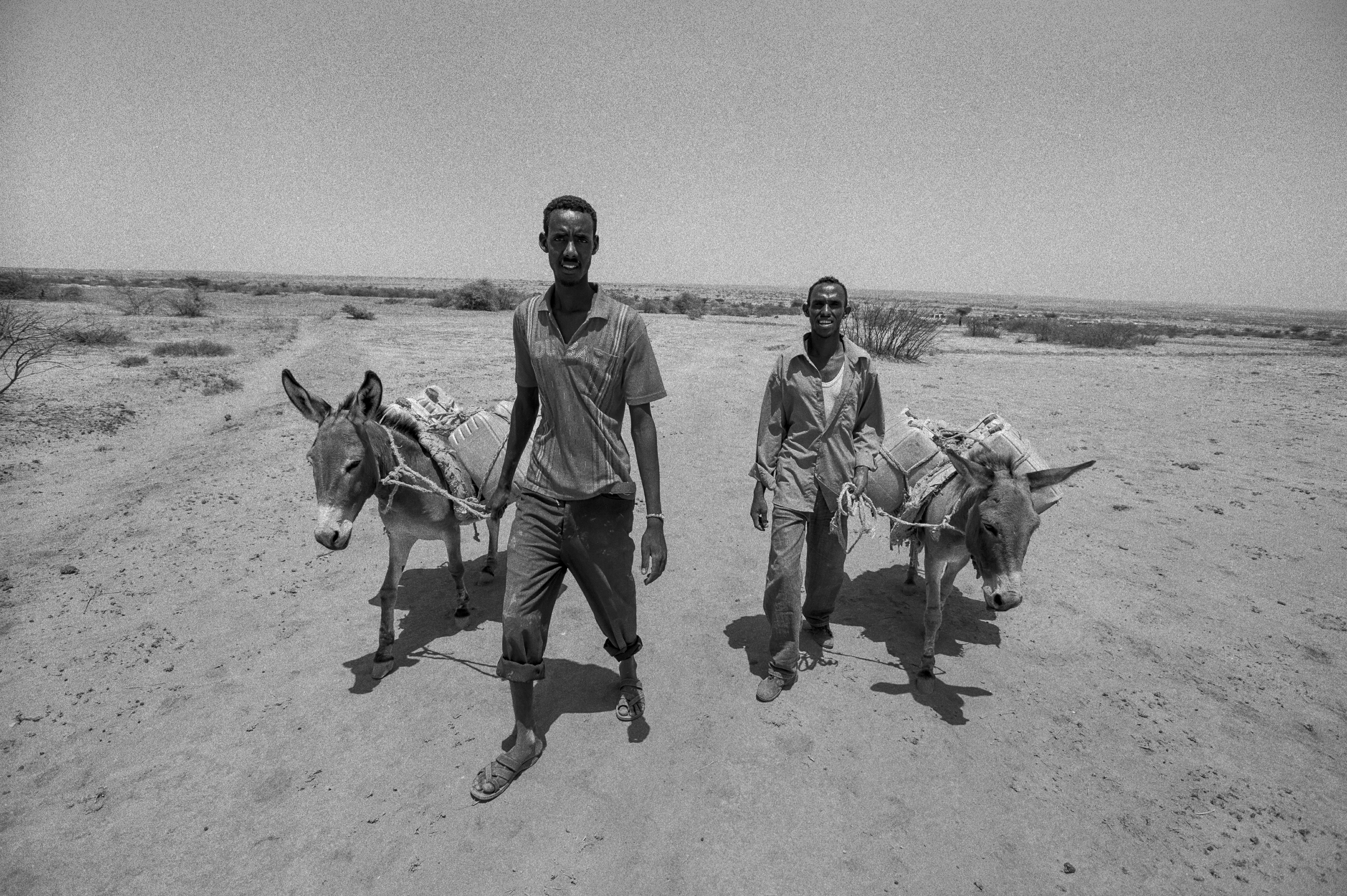 Two young men return to their village after traveling 25 miles to hunt for water. Photo by Sebastian Rich for UNICEF
