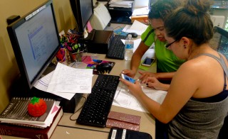 "Idaysy Briones, left, gets help filling out a federal financial aid form from fellow Valencia College student and ""financial learning ambassador,"" Karina Concepción. Photo by Timothy Pratt/ Hechinger Report"