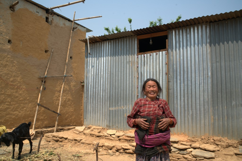 Shyam Maya Tamang is living in a metal sheet shelter until her house can be repaired. Photo courtesy of Mercy Corps