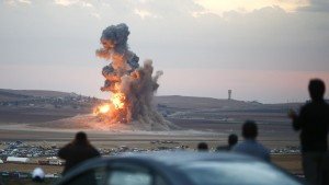 Smoke and flames rise over a hill near the Syrian town of Kobani after an airstrike, as seen from the Mursitpinar crossing on the Turkish-Syrian border in the southeastern town of Suruc in Sanliurfa province, October 23, 2014.  U.S. military forces again focused air strikes on the area near the Syrian city of Kobani in their campaign to turn back Islamic State forces and also hit oil facilities held by the militant group, the U.S. Central Command said on Thursday.     Photo By Kai Pfaffenbach/Reuters