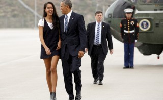 U.S. President Barack Obama and his daughter Malia walk in the rain from Marine One to board Air Force One upon their departure from Los Angeles, California April 8, 2016.    REUTERS/Kevin Lamarque  - RTSE85V