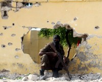 A Somali soldier takes position at the scene of a suicide attack by al Shabaab militants in capital Mogadishu June 21, 2015. Four Islamist gunmen were killed after detonating a car bomb and shooting their way into a national intelligence agency training site, the internal security ministry said, adding that the government did not suffer any casualties during the attack. REUTERS/Feisal Omar       TPX IMAGES OF THE DAY      - RTX1HFKT
