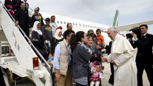 Pope Francis welcomes a group of Syrian refugees after landing at Ciampino airport in Rome following a visit at the Moria refugee camp in the Greek island of Lesbos, April 16, 2016. REUTERS/ Filippo Monteforte/Pool - RTX2A8KJ