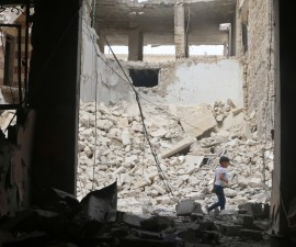 A child walks past damaged buildings after an airstrike in the rebel held area of Aleppo's Baedeen district, Syria, May 3, 2016. REUTERS/Abdalrhman Ismail - RTX2CNTZ