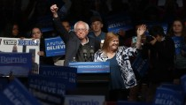 Democratic U.S. presidential candidate and U.S. Senator Bernie Sanders pumps his first in the air to the crowd after his wife Jane (R) came onstage and whispered in his ear as he spoke to supporters at a campaign event held during Indiana primary day at Waterfront Park in Louisville, Kentucky, U.S., May 3, 2016.   REUTERS/Aaron P. Bernstein   TPX IMAGES OF THE DAY - RTX2CPEG